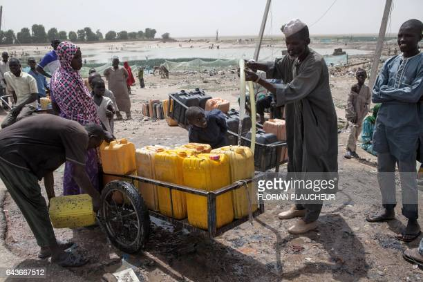 A cart pusher carries jerrycans with water from a borehole to supply people at a camp for Internal displaced people in Dikwa on February 15 2017...