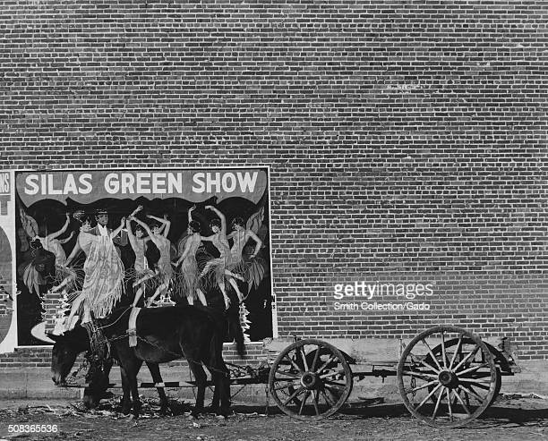 Cart with two donkeys in front of a large brick wall with a poster for a minstrel show with a dancing couple surrounded by dancing women titled Silas...