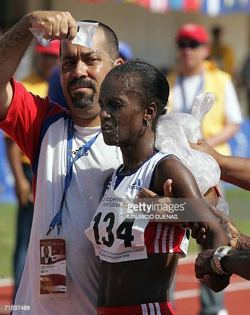 Yailen Garcia de Cuba es refrescada por su entrenador luego de cruzar la meta y ganar la medalla de plata en la prueba de maraton femenina durante...