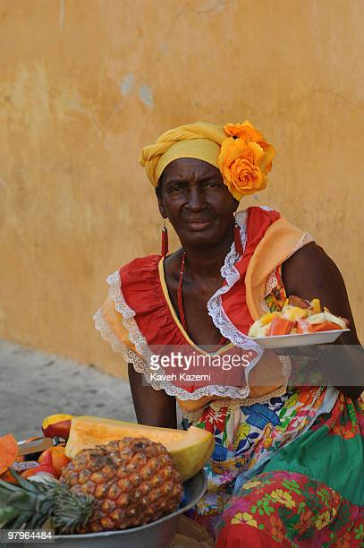 CARTAGENA of INDIAS COLOMBIA JANUARY 26 2010 A Cartagenan woman in a colorful traditional dress sells a plate of cut fresh fruits while sat on the...