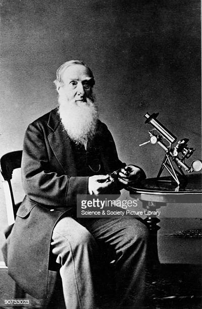 Carte de visite photograph by Wilson & Beadell of Charles Brooke seated at a table on which stands a microscope. Brooke is holding the turret part of...