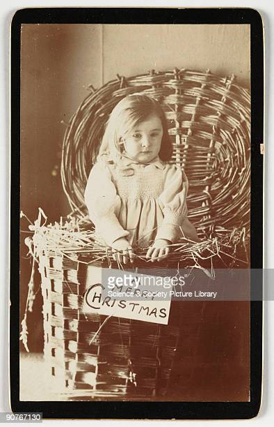 A cartedevisite Christmas card of a little girl in a wicker hamper taken by an unknown photographer in about 1875 A cartedevisite is a photograph...