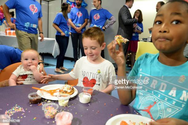 Carter Brendan and Daniel decorate donuts during Day of Joy Celebration at Boston Children's Hospital August 28 2017 in Boston Massachusetts