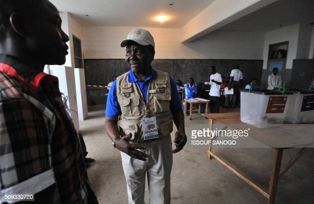 Carter Center Observer Chief former Nigerian President general Yakubu Gowon talks with a polling station staff member during the vote for...