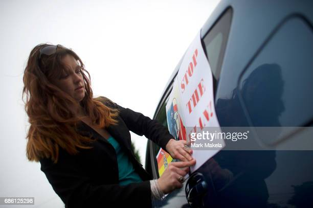 Carter Farmer affixes protest posters against the Klu Klux Klan to her car before driving in a caravan through the Quarryville area where the KKK...