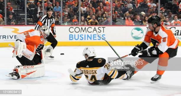 Carter Hart and Ivan Provorov of the Philadelphia Flyers react to a shot on goal against Jake DeBrusk of the Boston Bruins on March 10 2020 at the...