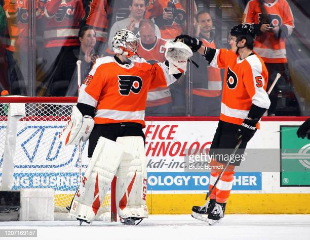 Carter Hart and Philippe Myers of the Philadelphia Flyers celebrate their 51 victory over the Columbus Blue Jackets at the Wells Fargo Center on...
