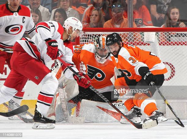 Carter Hart and Radko Gudas of the Philadelphia Flyers defend against Nino Niederreiter of the Carolina Hurricanes during the second period at the...