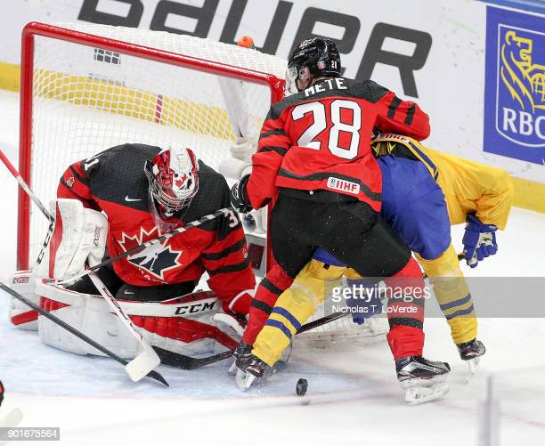 Carter Hart of Canada makes a save while Victor Mete clears a Sweden player from in front of the net during the first period of play in the IIHF...