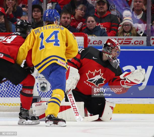 Carter Hart of Canada makes the save against Elias Pettersson of Sweden during the Gold medal game of the IIHF World Junior Championship at KeyBank...