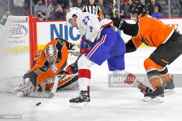 Carter Hart of the Lehigh Valley Phantoms pushes the puck away from the net with his stick while Alexandre Alain of the Laval Rocket tries to take...