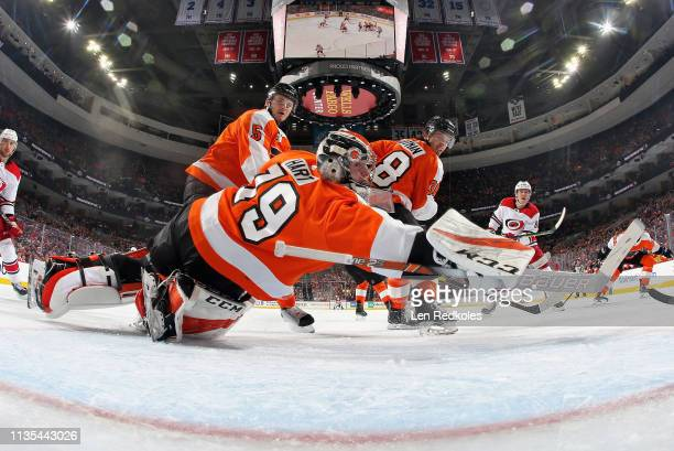 Carter Hart of the Philadelphia Flyers dives across his crease as Samuel Morin and Ryan Hartman look back into the net against the Carolina...