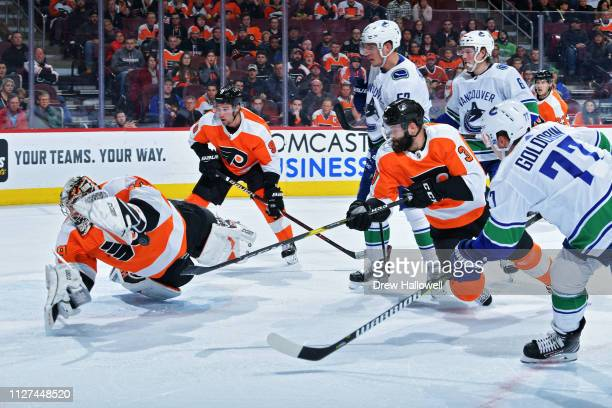 Carter Hart of the Philadelphia Flyers makes a diving save on a shot by Nikolay Goldobin of the Vancouver Canucks as Radko Gudas and Ivan Provorov of...
