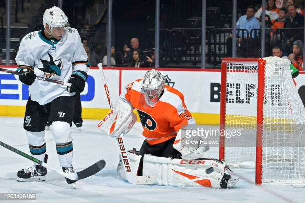 Carter Hart of the Philadelphia Flyers makes a save as Dylan Gambrell of the San Jose Sharks looks on in the second period at Wells Fargo Center on...