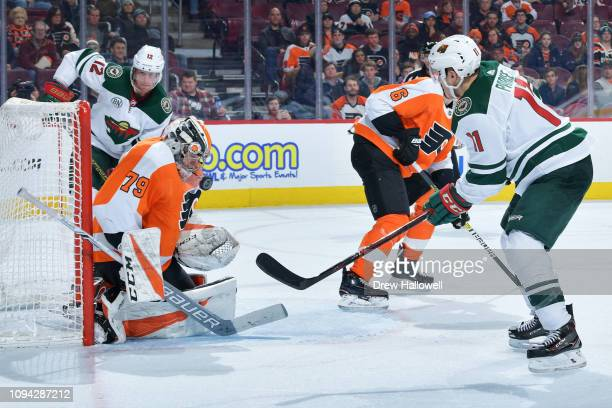 Carter Hart of the Philadelphia Flyers makes a save between Eric Staal and Zach Parise of the Minnesota Wild at Wells Fargo Center on January 14 2019...