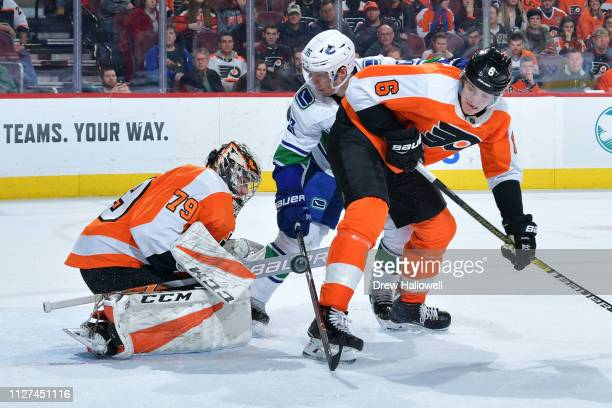 Carter Hart of the Philadelphia Flyers makes a save on a shot by Antoine Roussel of the Vancouver Canucks as Travis Sanheim defends during the third...