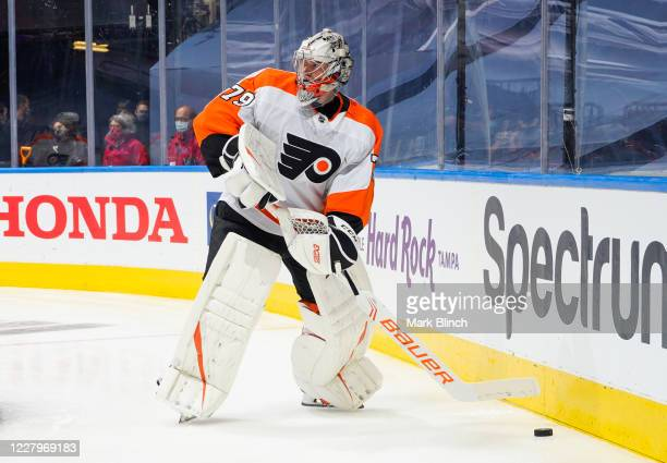 Carter Hart of the Philadelphia Flyers plays the puck against the Tampa Bay Lightning during the first period in an Eastern Conference Round Robin...