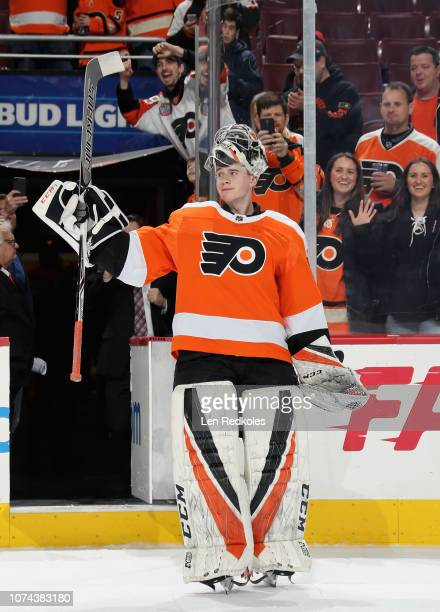 Carter Hart of the Philadelphia Flyers salutes the crowd after winning his NHL debut against the Detroit Red Wings by a score of 32 on December 18...