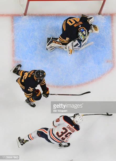 Carter Hutton and Rasmus Dahlin of the Buffalo Sabres defend against Alex Chiasson of the Edmonton Oilers during an NHL game on March 4 2019 at...