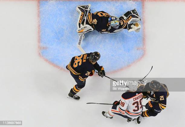 Carter Hutton makes a save as Rasmus Dahlin and Kyle Okposo of the Buffalo Sabres defend against Alex Chiasson of the Edmonton Oilers during an NHL...