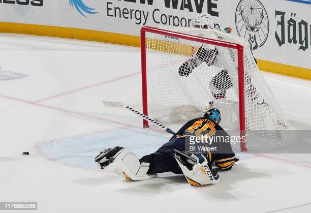 Carter Hutton of the Buffalo Sabres dives to sweep the puck away from Clayton Keller of the Arizona Coyotes during overtime of an NHL game on October...