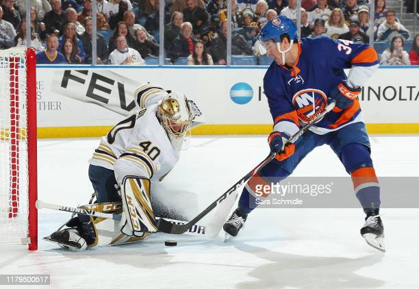Carter Hutton of the Buffalo Sabres makes a save against Cole Bardreau of the New York Islanders during an NHL game on November 2 2019 at KeyBank...