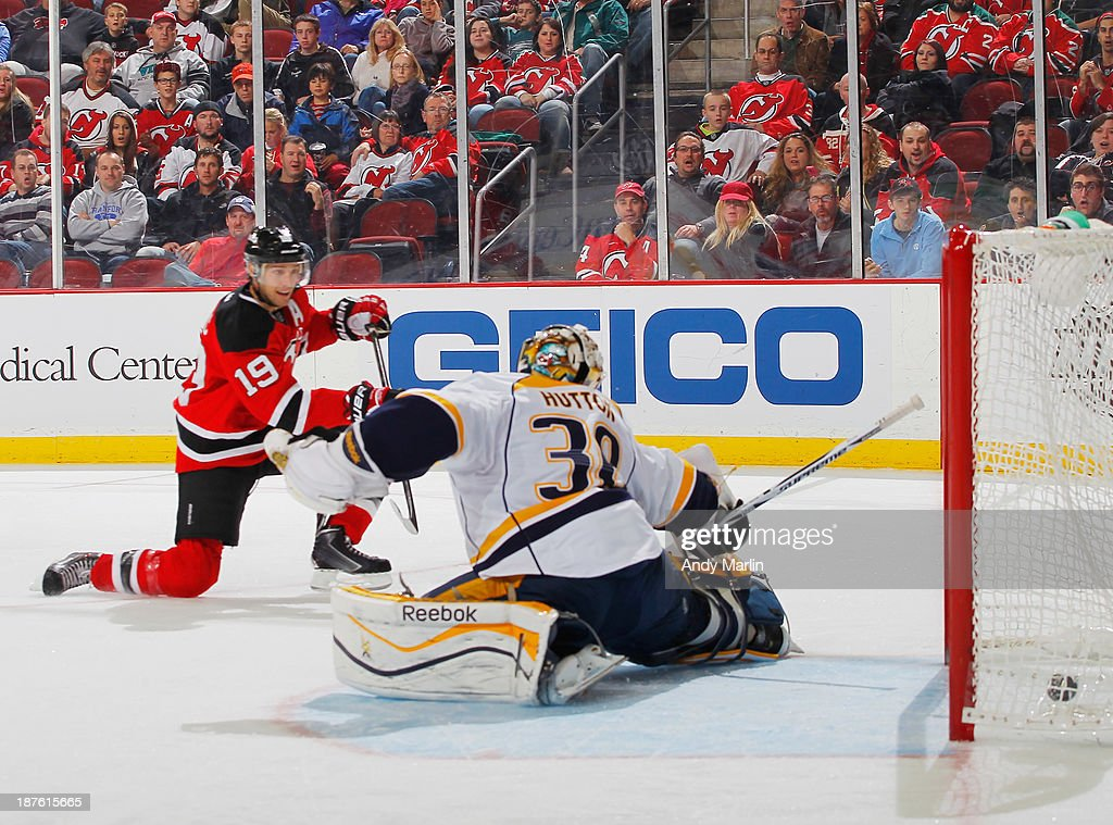 Carter Hutton #30 of the Nashville Predators cannot stop a goal by Travis Zajac #19 of the New Jersey Devils during the game at the Prudential Center on November 10, 2013 in Newark, New Jersey. That goal was Zajacs 100th career NHL regular season goal.