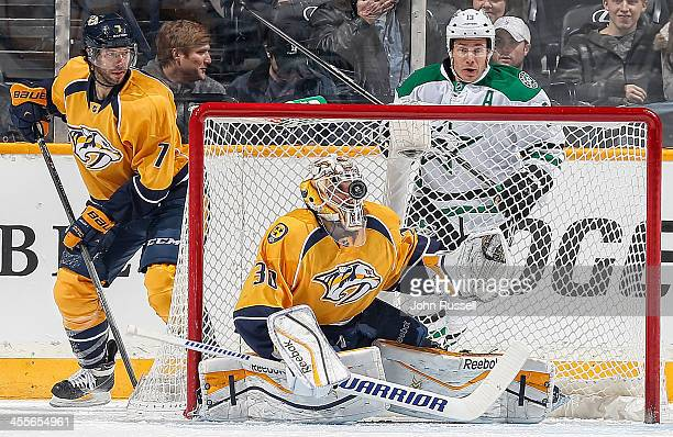 Carter Hutton of the Nashville Predators makes the save with his helmet against the Dallas Stars at Bridgestone Arena on December 12, 2013 in...