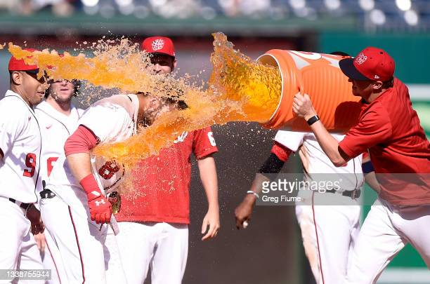 Carter Kieboom of the Washington Nationals is doused with gatorade by Erick Fedde after driving in the game winning run with a single in the ninth...