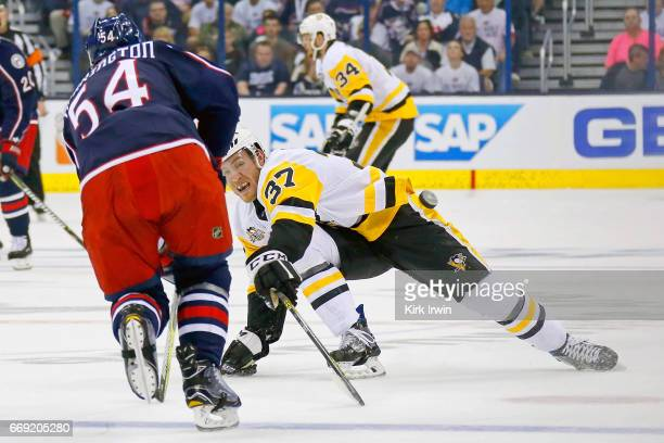 Carter Rowney of the Pittsburgh Penguins attempts to steal the puck from Scott Harrington of the Columbus Blue Jackets during the first period in...