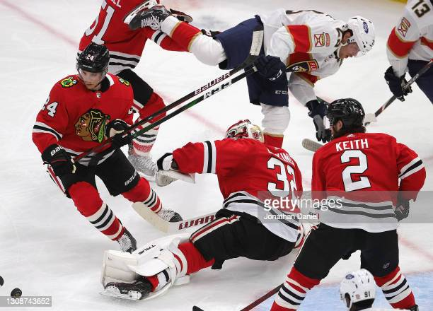 Carter Verhaeghe of the Florida Panthers falls over Kevin Lankinen of the Chicago Blackhawks after Lankinen made a save as Pius Suter and Duncan...