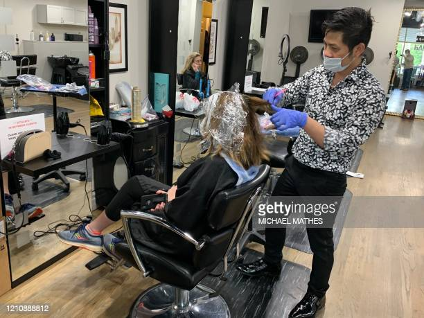 Carter Vu owner of an Atlanta hair salon bearing his name checks the hair color treatment on Ann Walsh on April 24 the first day such businesses were...