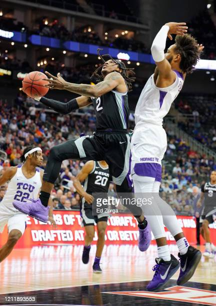 Cartier Diarra of the Kansas State Wildcats lays drives to the basket against PJ Fuller of the TCU Horned Frogs in the first half during the first...