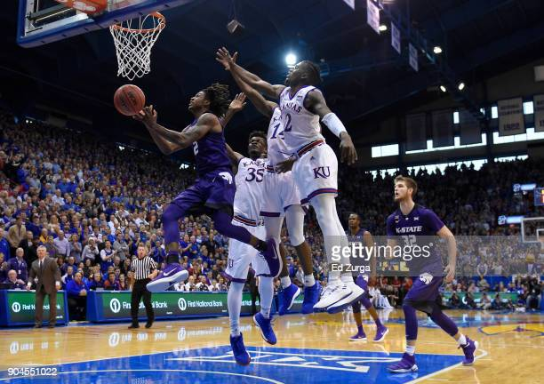 Cartier Diarra of the Kansas State Wildcats tries to the score against Udoka Azubuike Malik Newman and Lagerald Vick of the Kansas Jayhawks in the...