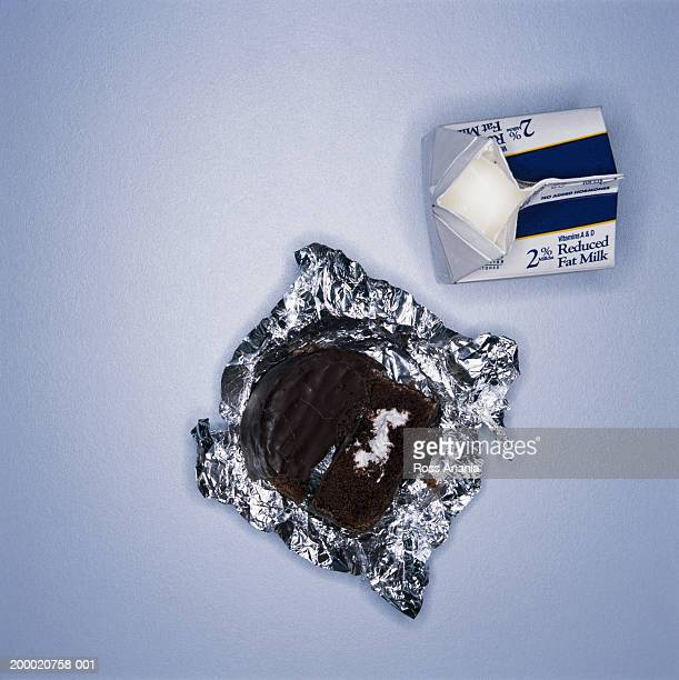 carton of milk beside chocolate dessert on foil wrapper - milk carton stock photos and pictures