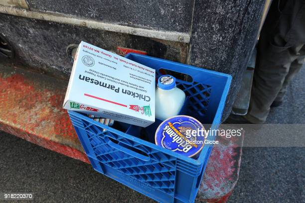 A carton sits on the rear step of his truck while Roger Barsamian goes through the freezer as he makes deliveries for Thatcher Farm in South Boston...