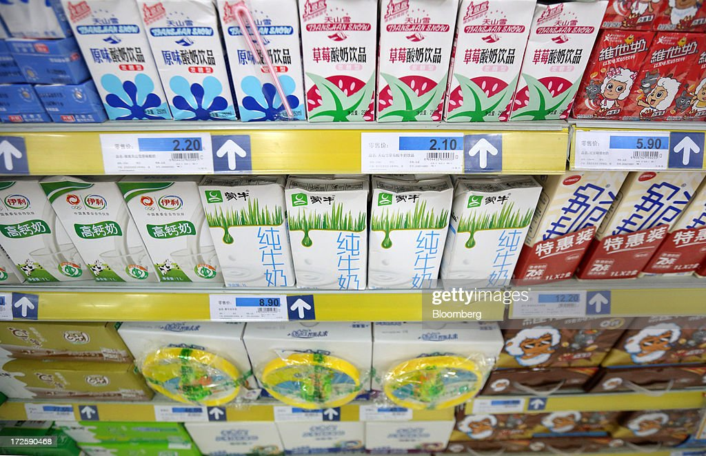 Cartons of China Mengniu Dairy Co. milk, center, are displayed for sale along with other brands at a store in Shanghai, China, on Tuesday, July 2, 2013. Banks including Goldman Sachs Group Inc. have pared their growth projections for China this year to 7.4 percent, below the government's 7.5 percent goal disclosed at the March conference at which Li Keqiang became premier. Photographer: Tomohiro Ohsumi/Bloomberg via Getty Images