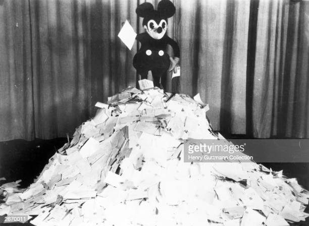 Cartoon character Mickey Mouse on top of a pile of letters that he has received from fans
