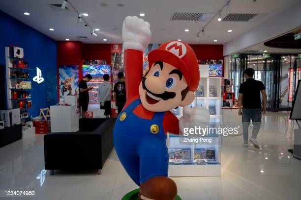 Cartoon figurine of Super Mario Bros. Stands in front of a Nintendo Switch store in a shopping market. By the end of June 2021, Nintendo's total...