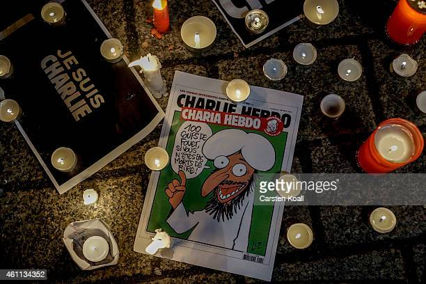 A cartoon lies on the ground while people gather at a vigil in front of the French Embassy following the terrorist attack in Paris on January 7 2015...