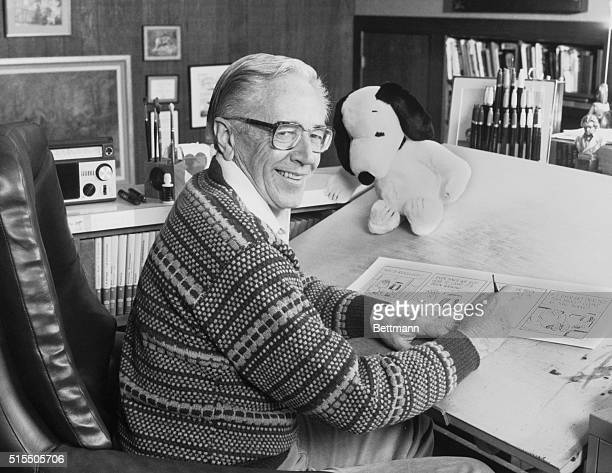 Cartoonist Charles M Schulz creator of the 'Peanuts' comic strip draws in his studio near a stuffed Snoopy toy His comic strip was celebrated in the...
