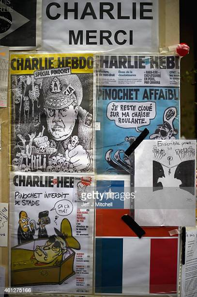 Cartoons are displayed in tribute as members of the public view flowers and tributes left near the offices of French satirical magazine Charlie Hebdo...