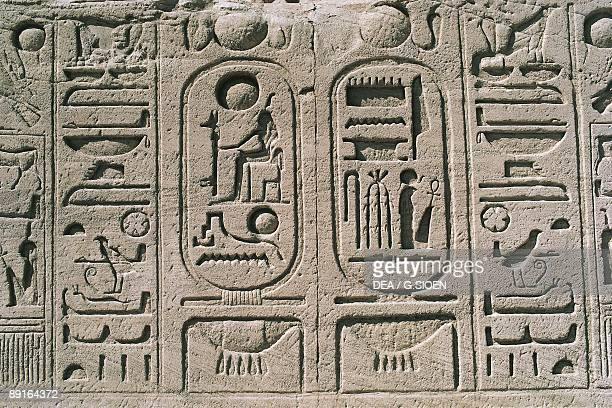Cartouches at base of colossal sandstone figures of enthroned Ramses II