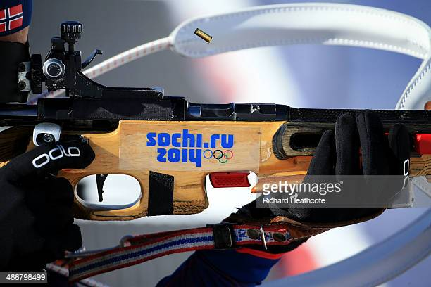 A cartridge flies out of a rifle as competitiors train for the biathlon ahead of the Sochi 2014 Winter Olympics at the Laura CrossCountry Ski and...