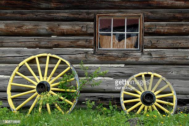 Cartwheels painted yellow in front of a log cabin, historic town Barkerville, British Columbia, Canada, North America