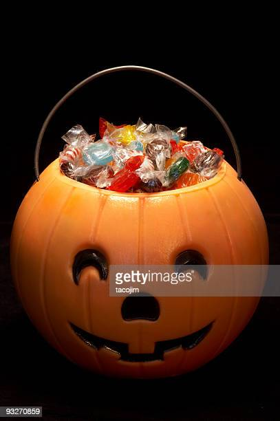 a carved hallowe'en pumpkin filled with candies - halloween candy stock photos and pictures