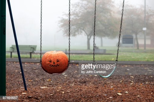 Carved pumpkin on swing in park