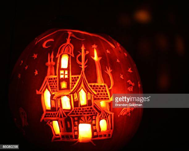 Carved pumpkin with haunted house