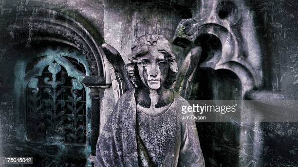 A carved stone angel stands beside the doorway of a mausoleum on the central avenue of Brompton Cemetery on December 17 2012 in London England Dead...