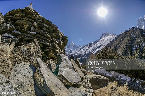 Carved stones on the base of a cairn and stupa in the Himalayas